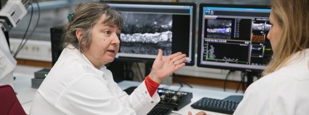 Två kvinnor i labbrockar diskuterar framför datorskärmar