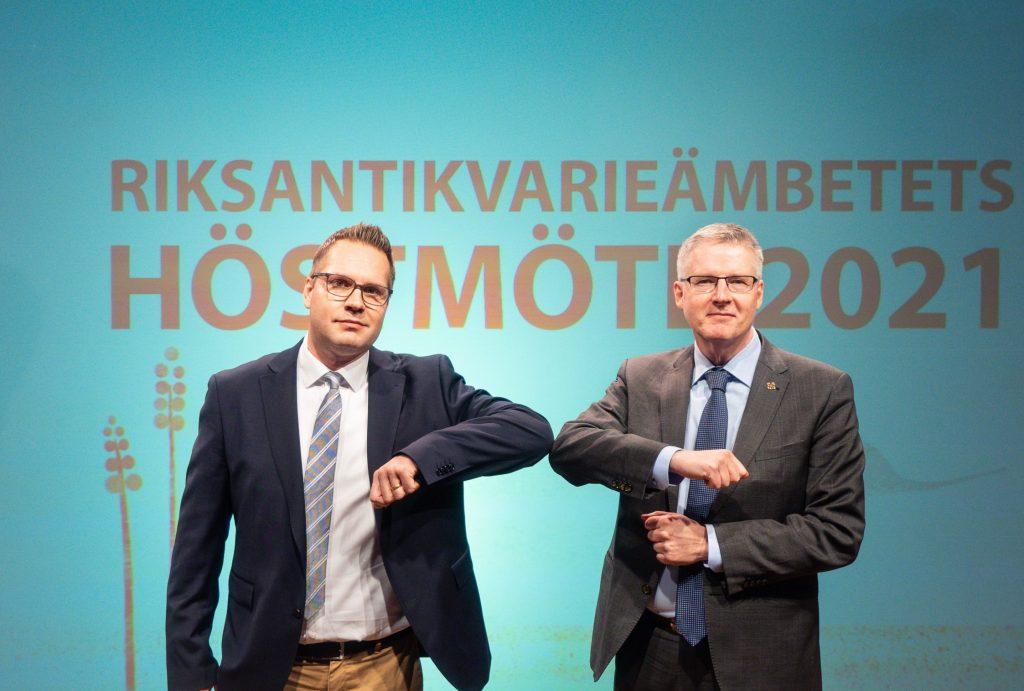 Två män i slips och kavaj hälsar varandra med armbågarna