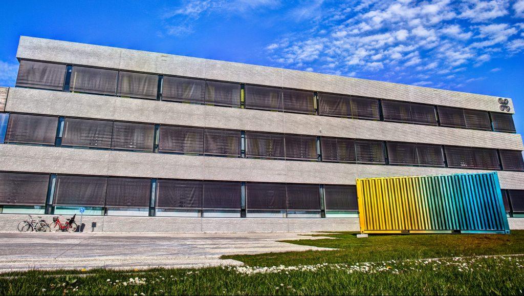 Bilden visar en fasaden vid ingången på Riksantikvarieämbets kontor i Visby. Framför står ett konstverk i regnbågens färger.