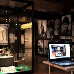 Museimonter med föremål och på bordet framför är en bärbar dator som på skärmen visar en bild av museimontern.