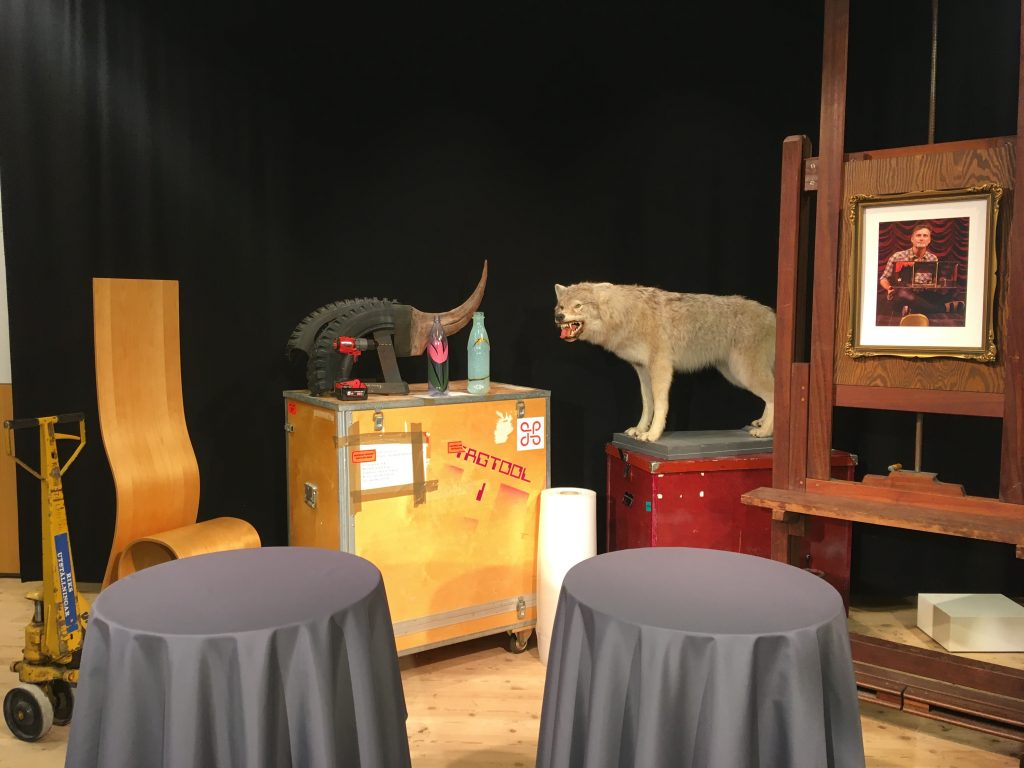 två ståbord framför packlådor, staffli. uppstoppad varg