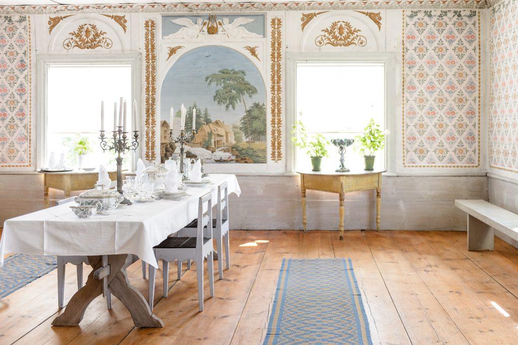 Interiör från matsalen med rikt illustrerade tapeter.Världsarvet Hälsingegårdar