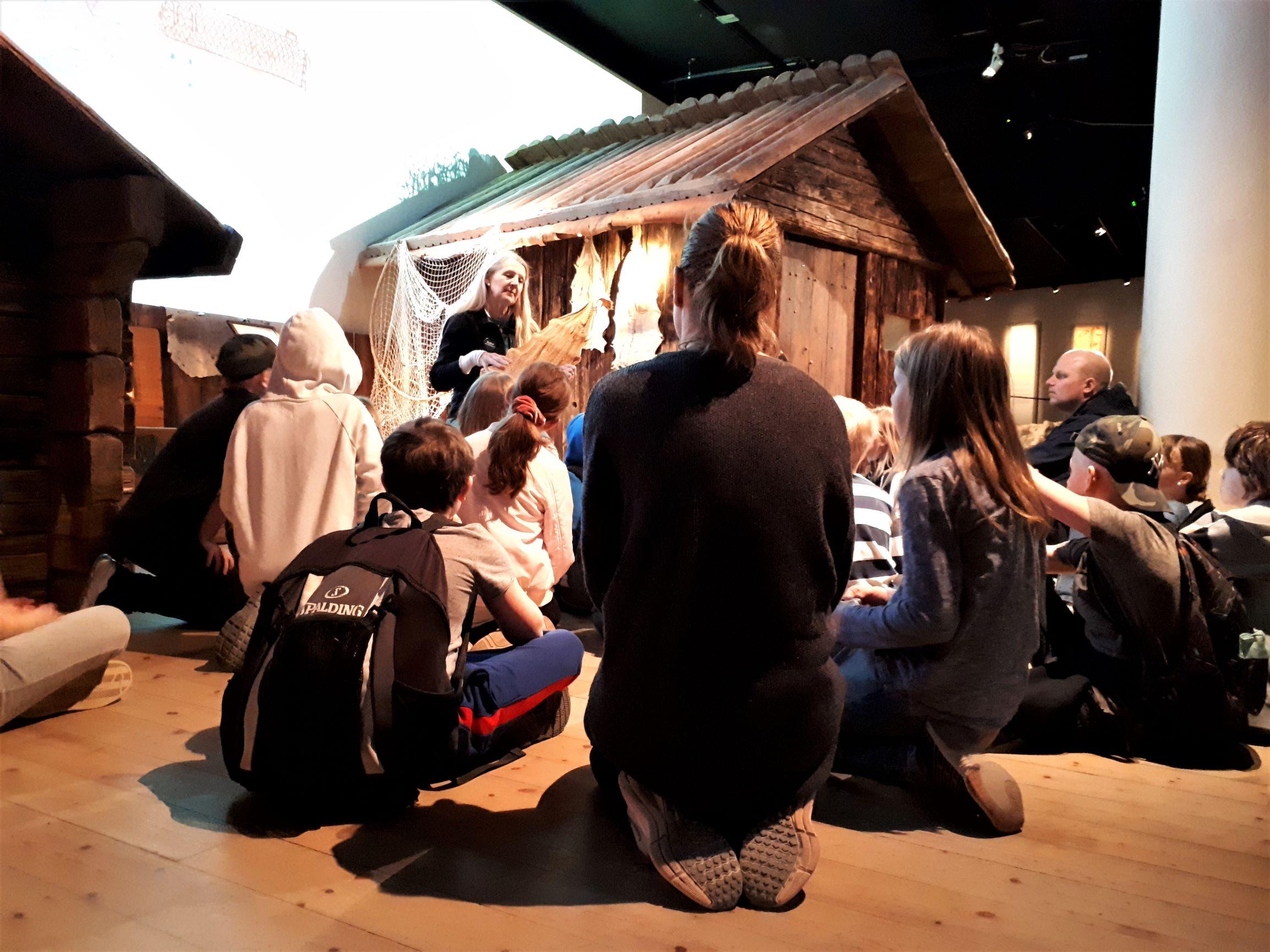 Barn som sitter på golvet framför en pedagog som visar upp ett föremål.
