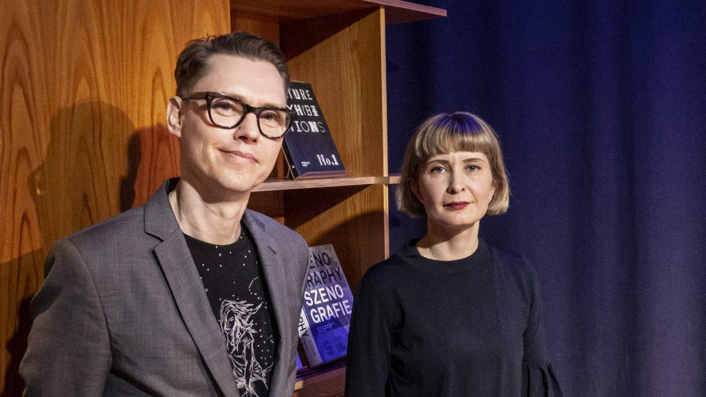 Fredrik och Lina framför en bokhylla.