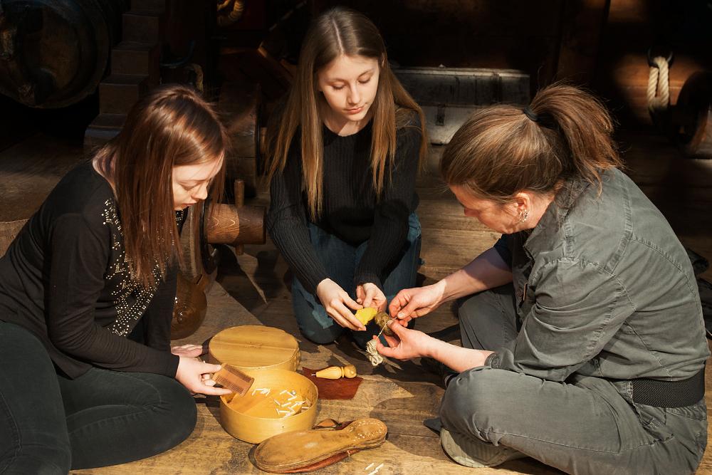 Tre kvinnor sitter på ett trädäck och lagar skor på traditionellt vis.