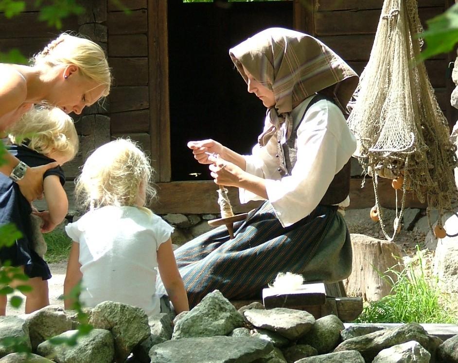 En kvinna i gammeldagsa kläder med huckle på huvudet håller i en slända som används till att spinna tråd. Hon visar den för en kvinna och hennes två små barn..