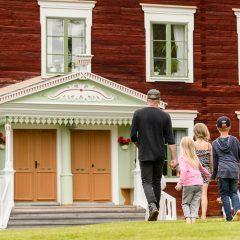 Man och tre barn är på väg in i ett hus.