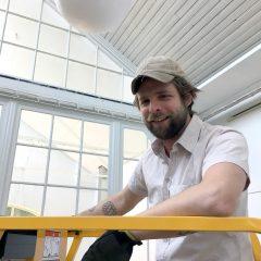 Simon deBrée utställningstekniker på Ronneby konsthall. Står på en gul lift i vit skjorta och keps.
