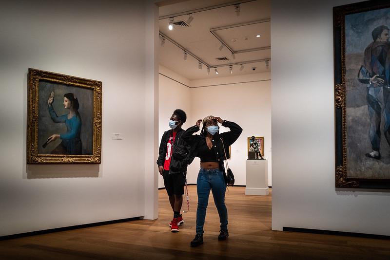 Två personer med munskydd ser sig om i en museilokal. På väggarna hänger tavlor.
