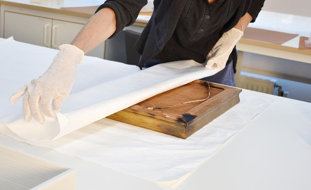 Handskklädda händer lägger ett vitt papper över en gammal ram.