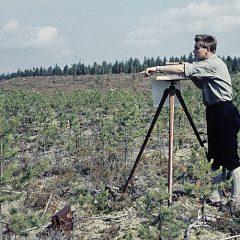 Man står i naturen med karteringsinstrument.