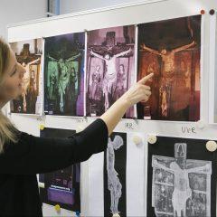 En ung kvinna med utsläppt hår studerar en röntgenfotografier på ett krucifix som sitter uppsatta på en whiteboardtavla.