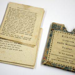 Gammal bok med lösa blad och med ett slitet bokomslagebredvid