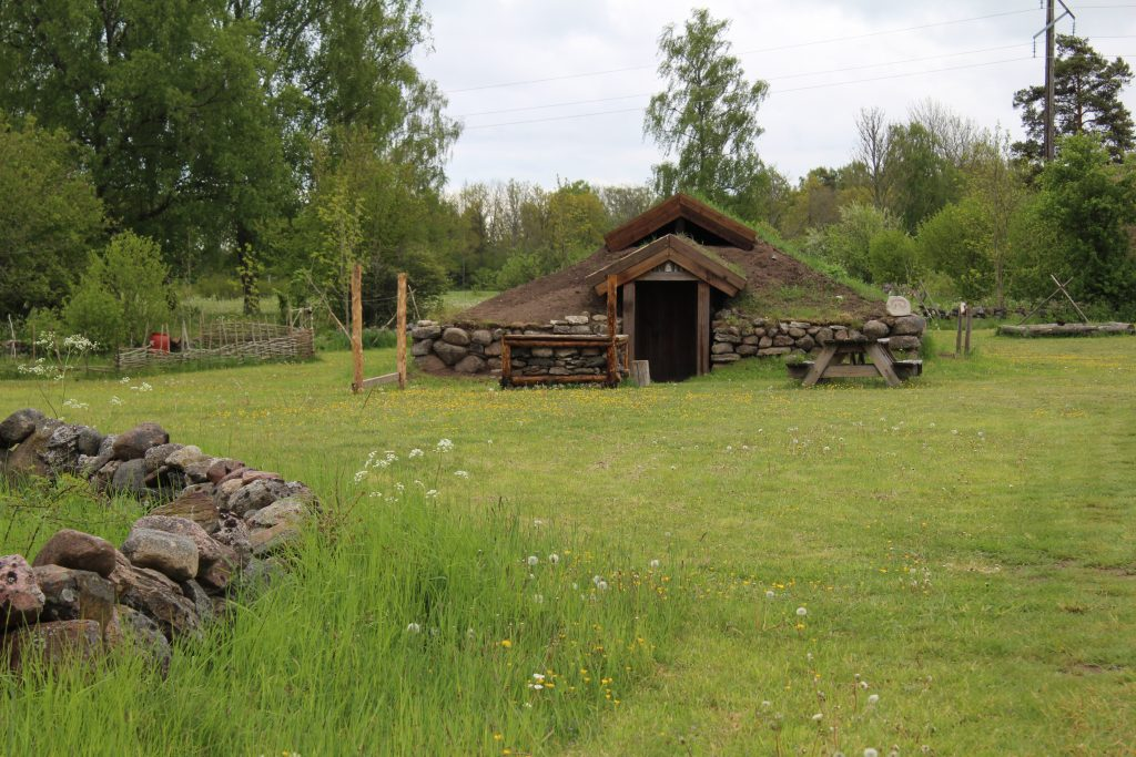 Foto på rekonstrerat järnåldershus med ingång på kortsida.